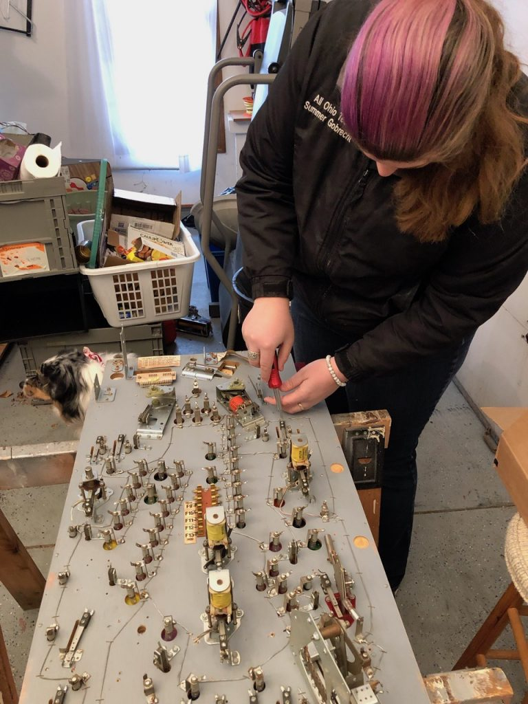 Competition shooter Summer Gobrecht refurbishing a pinball machine