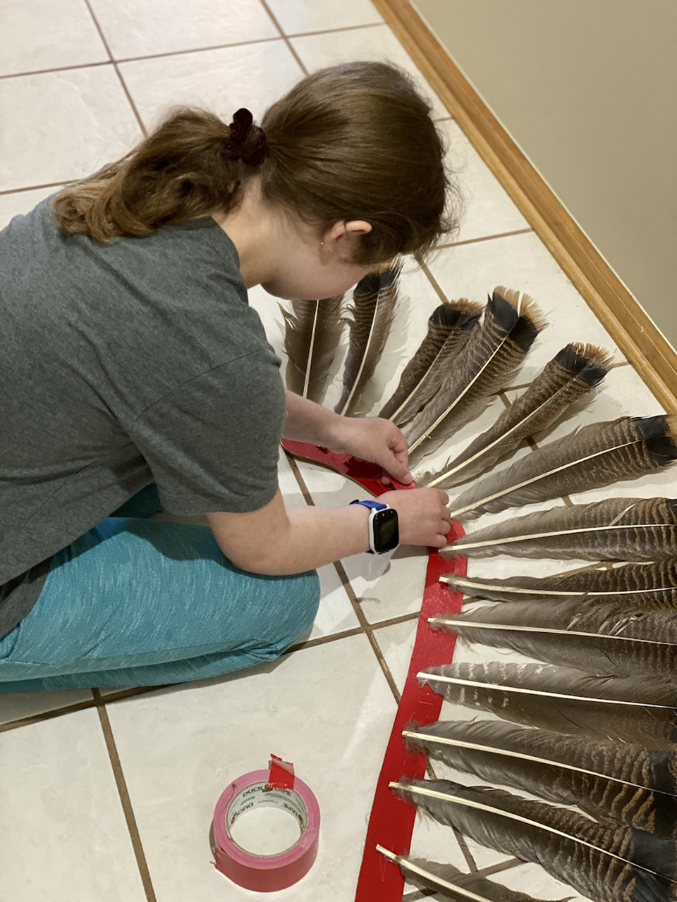 With the feathers glued to the supports, Anna adds duct tape for additonal support