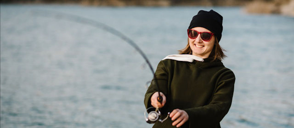 Fisherman with rod, spinning reel on the river bank. Fishing for pike, perch, carp. Woman catching a fish, pulling rod while fishing at the weekend. Girl fishing on lake, pond