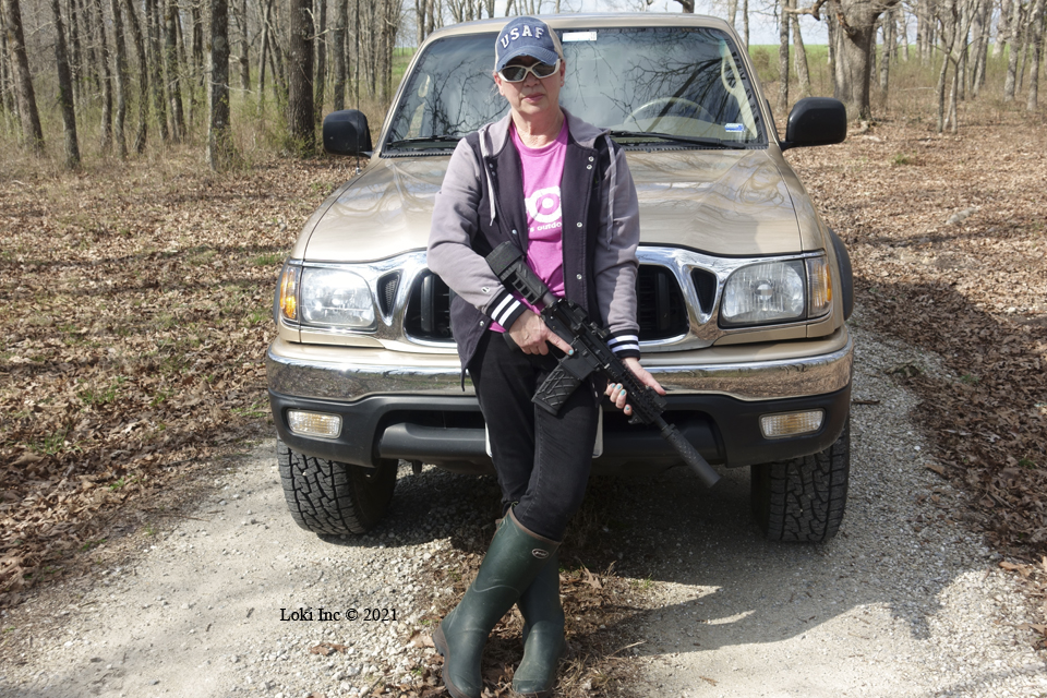 Barb with AR pistol suppressed in front of Tacoma truck Saker 556 ASR