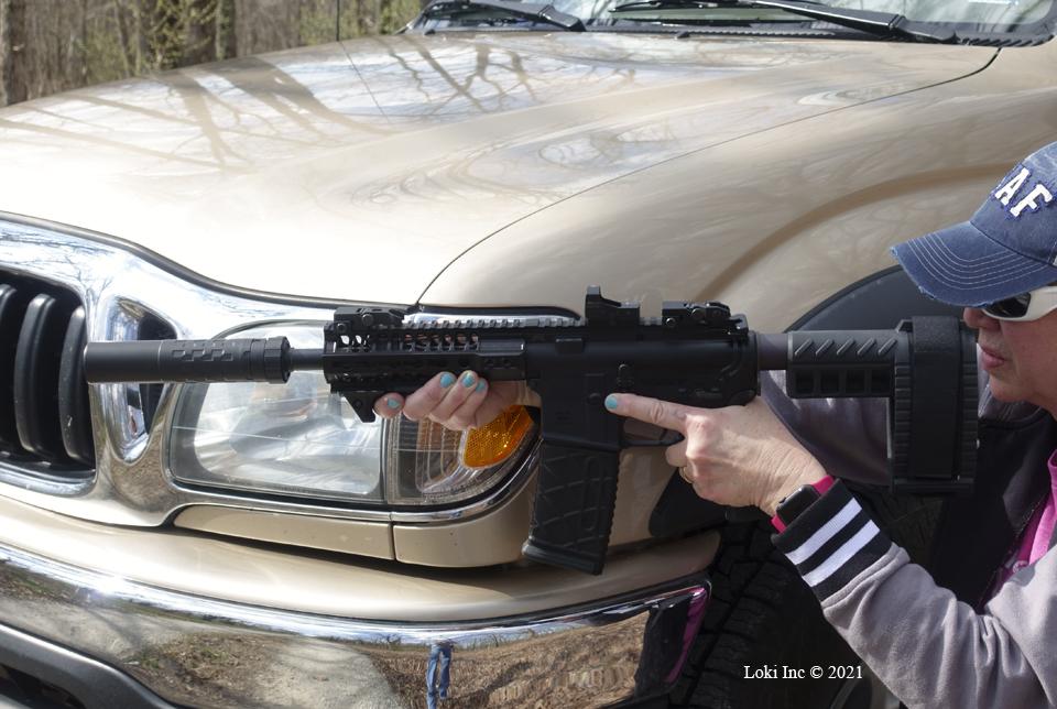 Barb with AR pistol suppressed kneeling against truck front quarter panel Saker 556 ASR