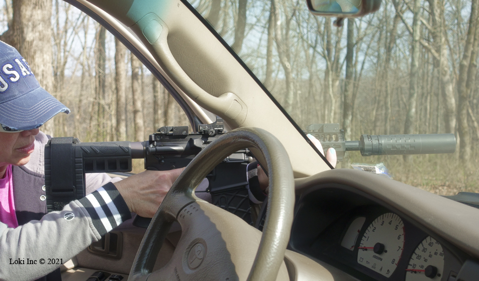 Barb with AR pistol suppressed using truck door and windshield pillar as support